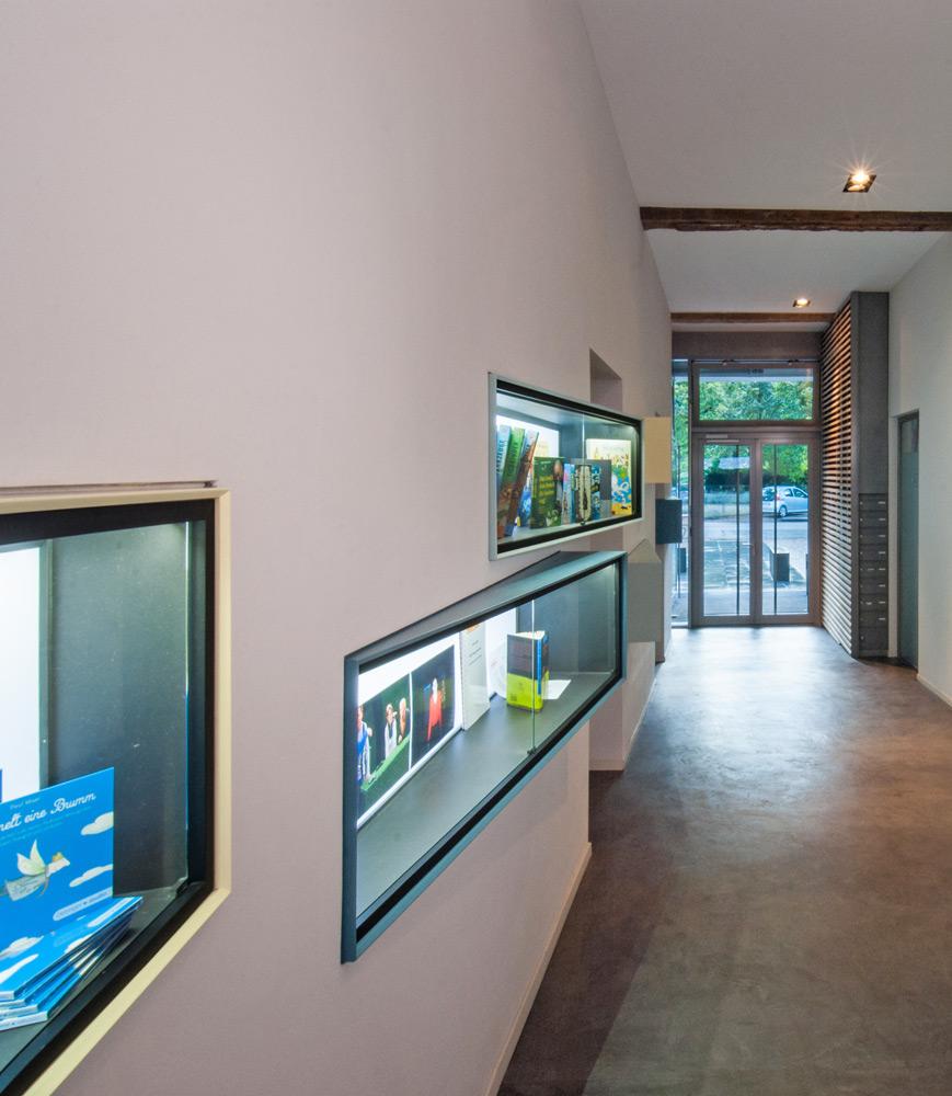 Ansicht zum Eingang eines Kinderbuchverlages mit Vitrinen von Roik Architekt