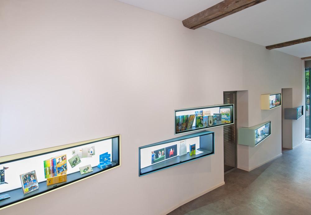 Spielerisch angeordnete Vitrinen im Eingangsbereich eines Kinderbuchverlages von Roik Architekt