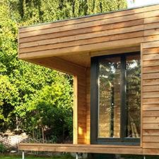 Gartenhaus im Grünen mit stützenfrei auskragender Ecke.